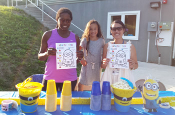 Crystal Run Healthcare Pediatricians, Dr. Jocelyn Dummett (left) and Dr. Lin-Lin Remenar (right), and Sydney Remenar (center) pose for a picture in front of the welcome table with a 'Healthy Tips' handout, at Friday night's event.