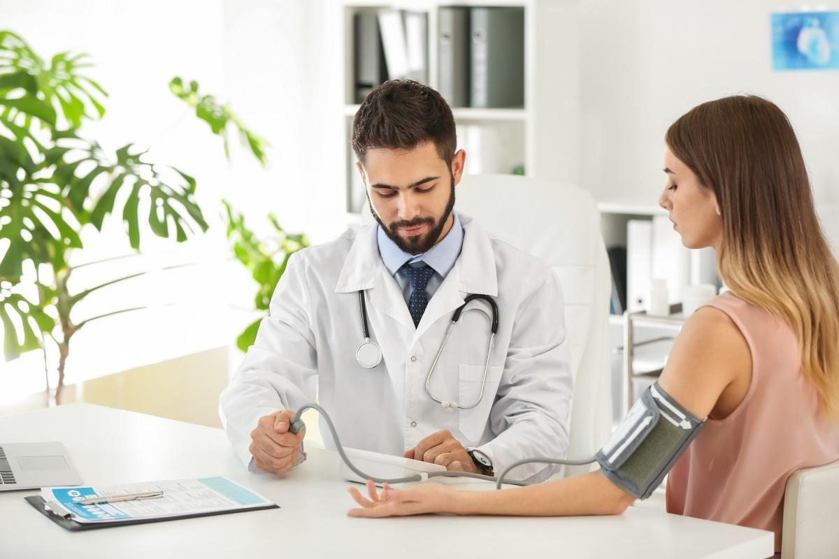 Male doctor working with female patient in clinic