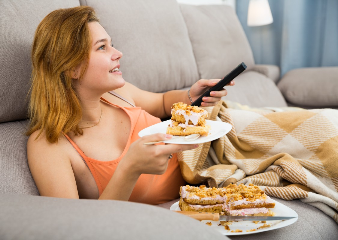 Young female eating sweet cake at home on sofa with tv remote